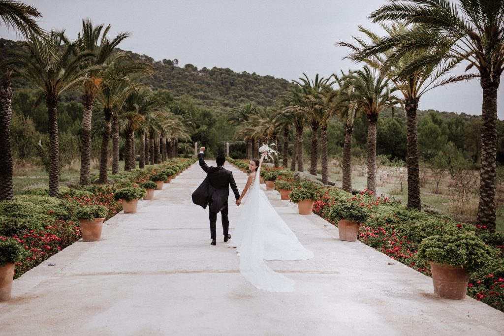 Bride and groom walk down the driveway in front of Hotel Son Claret in Mallorca