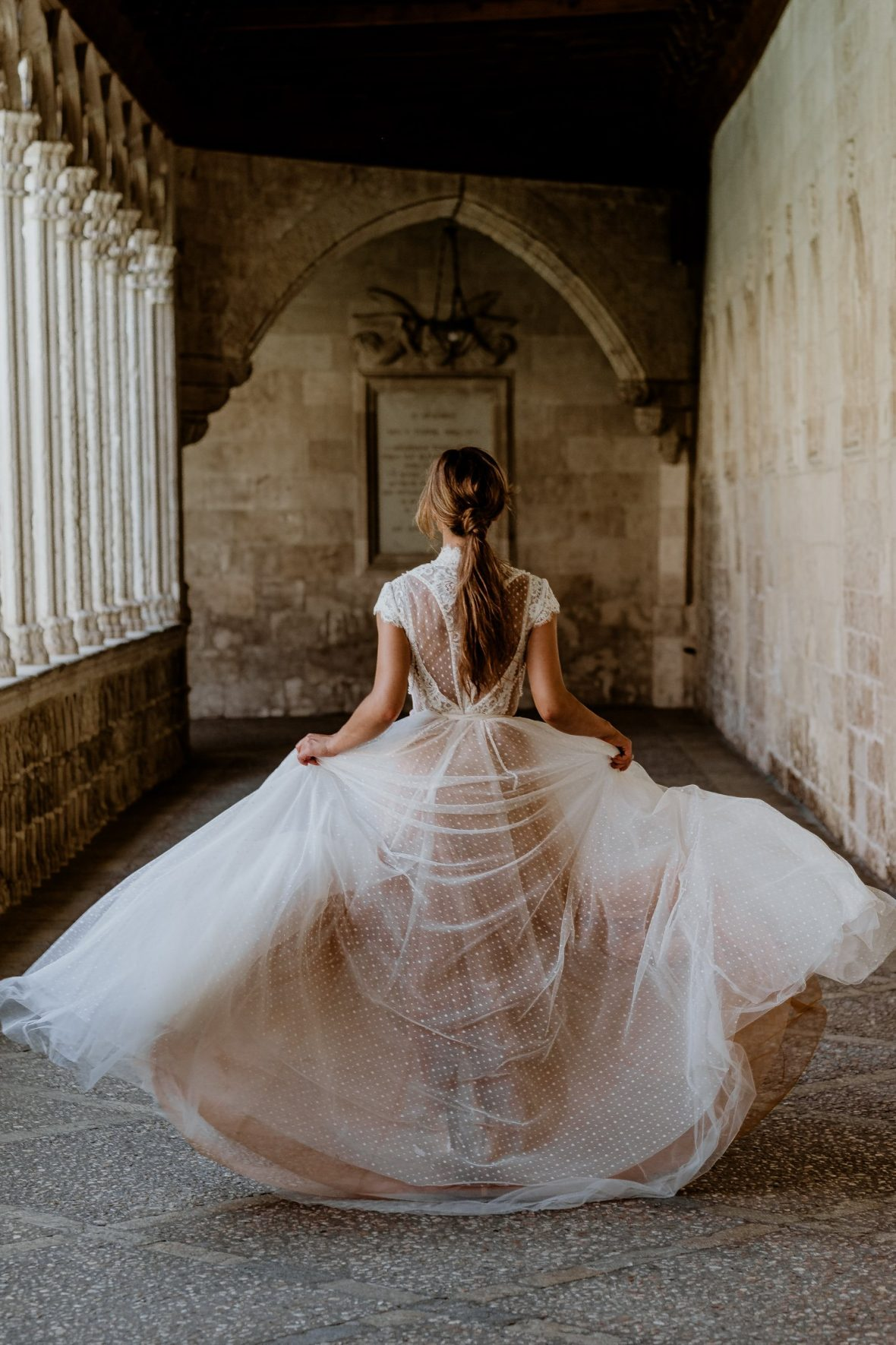 Bride walking gracefully through the cloister of Basilica de Sant Francesc d'Assís