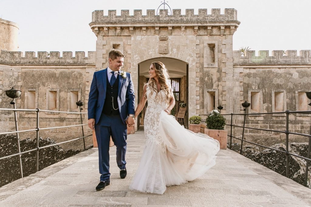 Bride and groom walk hand in hand in front of Cap Rocat's iconic entrance