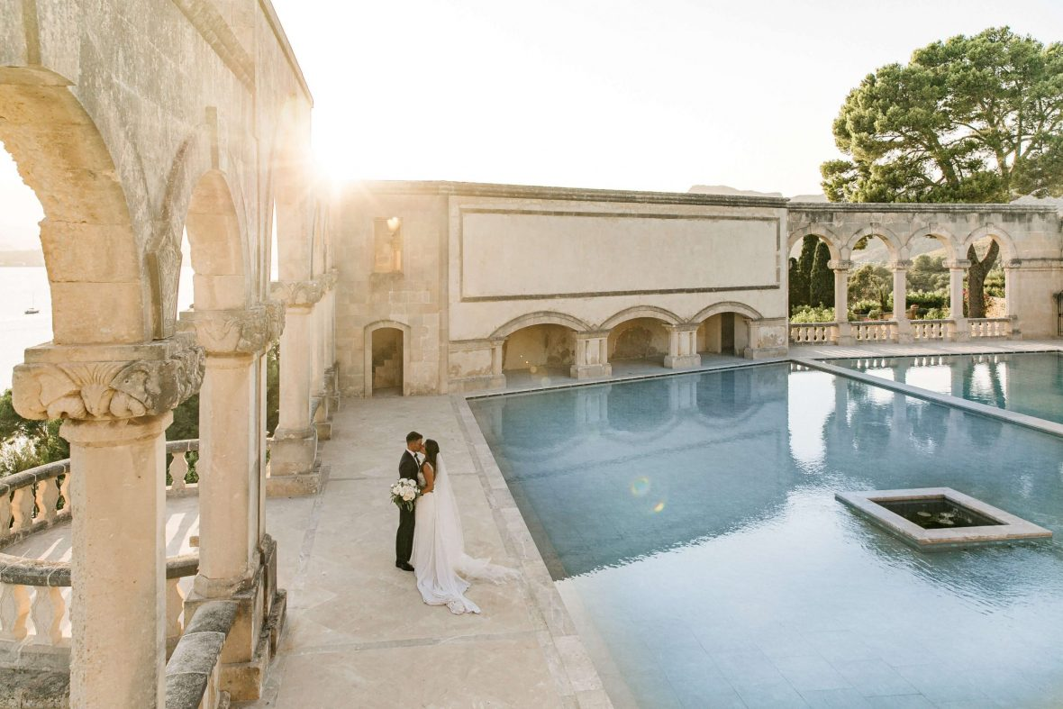 Newlyweds enjoying a kiss at their Mallorca wedding venue La Fortaleza in Pollensa during sunset