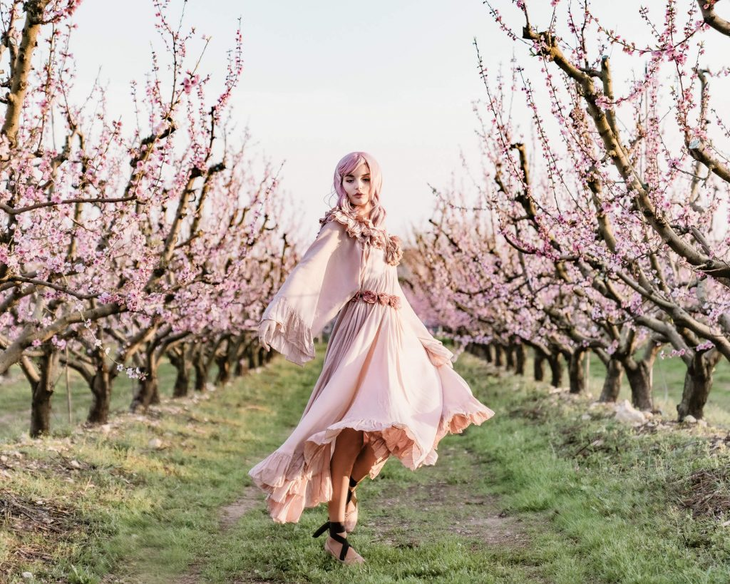Fashion editorial shooting of a girl walking through apricot blossoms as if in a fairytale