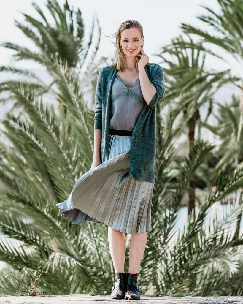 Young woman standing in the wind in front of palm trees in Palma de Mallorca for a fashion shoot